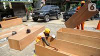 Petugas PPSU menyelesaikan pembuatan peti jenazah di Kantor Kelurahan Kayu Putih, Jakarta, Selasa, (6/7/2021). Kelurahan Kayu Putih berinisiatif membuat peti jenazah dilatar belakangi warganya yang terkendala ketersediaan peti saat angka kematian COVID-19 meningkat. (Liputan6.com/Faizal Fanani)