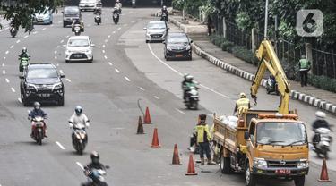 Petugas dari Dinas Bina Marga mengerjakan perbaikan jalan berlubang di Jalan DI Panjaitan, Cawang, Jakarta, Senin (25/1/2021). Perbaikan jalan rusak dan berlubang akibat sering tergenang banjir di kawasan tersebut untuk mengantisipasi terjadinya kecelakaan pengendara. (merdeka.com/Iqbal S Nugroho)