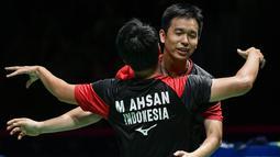 Ganda putra Indonesia Hendra Setiawan (kanan) dan Mohammad Ahsan merayakan kemenangan atas ganda putra Jepang Takuro Hoki dan Yugo Kobayashi pada babak final Kejuaraan Dunia Bulu Tangkis 2019 di Swiss, Minggu (25/8/2019). Ahsan/Hendra menang dengan skor 25-23, 9-21, 21-15. (FABRICE COFFRINI/AFP)
