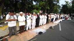 Massa pendukung pasangan capres-cawapres Prabowo Subianto dan Sandiaga Uno melakukan salat asar di Jalan Medan Merdeka Barat, Jakarta, Kamis (27/6/2019). Aksi tersebut dilakukan jelang putusan perselisihan hasil pemilihan umum (PHPU) Pilpres 2019 di Gedung MK. (merdeka.com/Arie Basuki)