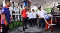 Presiden Joko Widodo (tengah) menyaksikan petugas mengisikan bahan bakar ke kendaraan saat meresmikan Implementasi Program Biodiesel 30 persen (B30) di SPBU MT Haryono, Jakarta, Senin (23/12/2019). Jokowi menargetkan implementasi program B40 pada 2020 dan B50 pada 2021. (Liputan6.com/Angga Yuniar)