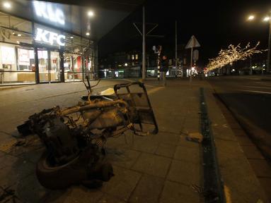 Skuter yang terbakar tergeletak di trotoar di luar restoran cepat saji yang hancur sebagai protes terhadap jam malam nasional di Rotterdam, Belanda, Senin (25/1/2021). Mulai 23 Januari, jam malam dimulai di Belanda dari pukul 21.00 hingga 04.30 untuk mengendalikan COVID-19. (AP Photo/Peter Dejong)