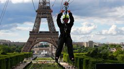 Pengunjung meluncur dengan seutas tali saat menjajal Zip Line dari lantai dua Menara Eiffel di atas taman Champ de Mars, Paris, Selasa (28/5/2019). Lintasan ini memungkinkan traveler untuk meluncur melintasi satu tempat ke tempat lainnya menggunakan tali dan alat olahraga outdoor. (AP/Francois Mori)