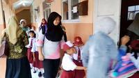 Emak-emak ikut mengantre di depan kelas, untuk peroleh bangku di hari pertama sekolah. (Foto: Liputan6.com/Muhamad Ridlo)