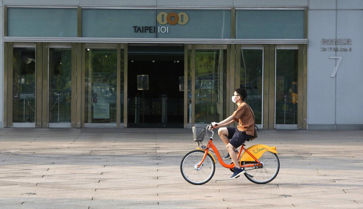 Seorang pria memakai masker untuk melindungi diri dari penyebaran COVID-19 saat bersepeda melewati Gedung Taipei 101 di Taipei, Taiwan, Sabtu (15/5/2021). Pandemi COVID-19 di Taiwan naik ke level tiga. (AP Photo/Chiang Ying-ying)
