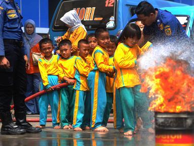 Petugas mendampingi siswa TK di lingkungan Kabupaten Bogor yang mencoba alat pemadam kebakaran di kantor Dinas Pemadam Kebakaran, Jalan Tegar beriman, Cibinong, Rabu (18/9/2019). Kegiatan belajar di luar kelas ini untuk mengenalkan profesi dan tugas pemadam kebakaran. (merdeka.com/Arie Basuki)