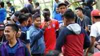 Gelandang Arema, Makan Konate, ketika melayani permintaan foto dari Aremania di Kebun Raya Purwodadi, Pasuruan. (Bola.com/Iwan Setiawan)