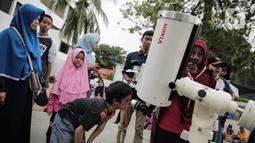 Pengunjung mengamati gerhana matahari cincin menggunakan teleskop di Planetarium Taman Ismail Marzuki, Jakarta, Kamis (26/12/2019). Planetarium menyediakan sekitar 10 teleskop dan kacamata khusus agar pengunjung bisa menyaksikan gerhana matahari cincin dengan aman. (Liputan6.com/Faizal Fanani)