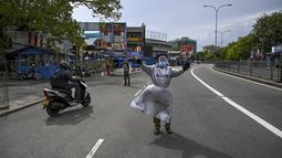 Seorang polisi memberi isyarat kepada pengendara di jalan setelah pemerintah memberlakukan pembatasan perjalanan dan lockdown akhir pekan di Kolombo, Sri Lanka, Sabtu (22/5/2021). Sri Lanka pada Jumat, 21 Mei mencatat 3.547 kasus harian corona Covid-19. (Ishara S. KODIKARA/AFP)