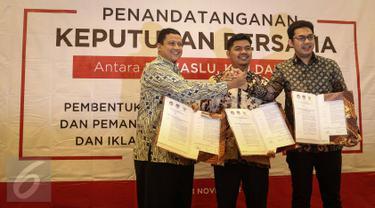 (ki-ka) Ketua Bawaslu Muhammad, Ketua KPU Juri Ardiantoro, Ketua KPI Yuliandre Darwis menunjukan surat usai menandatangani Keputusan Bersama Antara Bawaslu, KPU, Dan KPI di Jakarta, Jumat (11/11). (Liputan6.com/Faizal Fanani)