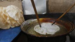 """Seorang pedagang Suriah menggoreng panekuk tradisional yang dikenal sebagai """"Naaem"""" yang biasa disajikan selama Ramadhan, di Shaqhoor Damaskus pada 28 April 2021. Betapa pun beratnya keadaan ekonomi, naeem adalah jawaban dari tradisi yang tidak bisa ditinggalkan selama Ramadhan. (LOUAI BESHARA/AFP)"""
