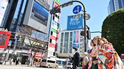 Seorang wanita berpakaian kimono (kanan) mengambil foto saat dirinya dan yang lain menunggu untuk menyeberangi persimpangan pejalan kaki yang terkenal di distrik Shibuya, Tokyo pada 20 Maret 2019. (Photo by CHARLY TRIBALLEAU / AFP)