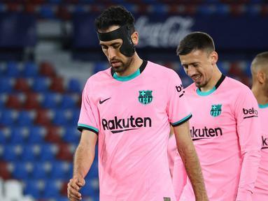 Ekspresi kecewa gelandang Barcelona, Sergio Busquets dan kawan-kawan usai ditahan imbang 3-3 oleh Levante dalam laga lanjutan Liga Spanyol 2020/2021 pekan ke-36 di Ciutat de Valencia Stadium, Valencia, Selasa (11/5/2021). (AFP/Jose Jordan)