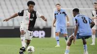 Pemain Juventus, Juan Cuadrado, berusaha melewati pemain Lazio pada laga Serie A di Stadion Allianz, Turin, Senin (20/7/2020). Juventus menang 2-1 atas Lazio. (AP/Marco Alpozzi)