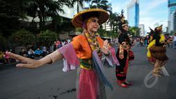 Seorang penari T-Ta menari saat car free day di Bundara HI, Jakarta, Minggu (26/4/2015). Mereka meminta sumbangan kepada warga untuk mengikuti Interntional Folklore Festival di Spanyol. (Liputan6.com/Faizal Fanani)