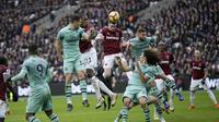 Pemain West Ham United, Declan Rice, melepaskan tandukan udara saat melawan Arsenal pada laga Premier League di Stadion London, Sabtu (12/1). West Ham United menang 1-0 atas Arsenal. (AP/Tim Ireland)