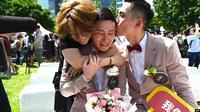 Shane Lin (tengah) dihibur oleh pasangannya Marc Yuan (kanan) dan seorang teman dalam upacara pernikahan sesama jenis di Distrik Shinyi di Taipei, Taiwan, 24 Mei 2019. (Sam Yeh/AFP)