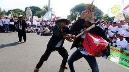Petani tebu melakukan aksi tearikal saat unjuk rasa di depan Istana Merdeka, Jakarta, Senin (28/8). Aksi ini dilakukan lantaran dinilai belum ada upaya pemerintah membantu petani, khususnya harga gula lokal yang semakin rendah. (Liputan6.com/Angga Yuniar)