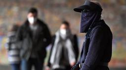 Komuter berjalan melewati Stasiun Flinders Street pada hari pertama wajib masker di tempat umum, di Melbourne, Kamis (23/7/2020). Penduduk kota terpadat kedua di Australia, Melbourne, diwajibkan mengenakan masker ketika meninggalkan rumah untuk mencegah penyebaran COVID-19. (William WEST/AFP)