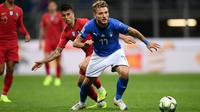 Striker Italia, Ciro Immobile membawa bola dari kawalan bek Portugal, Joao Cancelo selama pertandingan UEFA Nations League di Stadion San Siro di Milan (17/11). Italia bermain imbang 0-0 atas Portugal. (AFP Photo/Marco Bertorello)
