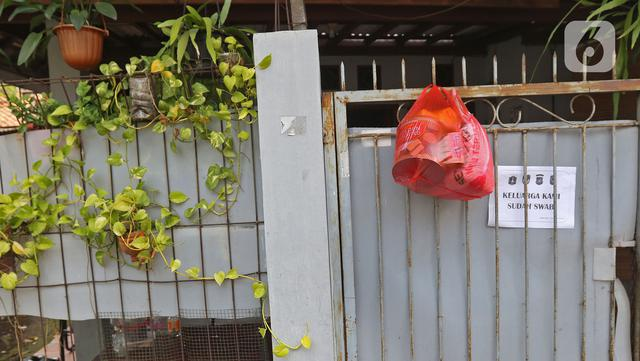 Bantuan bahan pokok kepada pasien positif Covid-19 yang melakukan isolasi mandiri di rumahnya terlihat di pagar di RT03/RW03, Kelurahan Cilangkap, Jakarta, Jumat (21/5/2021). (Liputan6.com/Herman Zakharia)