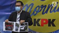 Penyidik KPK menunjukan barang bukti saat konferensi pers terkait Operasi Tangkap Tangan (OTT) atas kasus dugaan suap bansos penanganan covid-19 Kementerian Sosial, di Jakarta, Minggu (6/12/2020) dini hari. Kasus ini menjerat Mensos Juliari Batubara jadi tersangka. (Liputan6.com/Herman Zakharia)