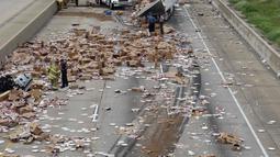 Sebuah truk pembawa pizza beku kehilangan kendali setelah melintasi jembatan di Jalan Raya Arkansas, Amerika Serikat, 9 Agustus 2017. Truk itu pun terbalik dan membuat pizza beku berserakan di jalanan. (Arkansas Department of Transportation via AP)