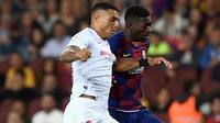 Bek Sevilla Diego Carlos berebut boa dengan winger Barcelona, Ousmane Dembele dalam pertandingan pekan kedelapan kompetisi La Liga Spanyol 2019-2020 di Camp Nou, Minggu (6/10/2019). Barcelona berhasil menang telak atas Sevilla dengan skor 4-0. (Josep LAGO / AFP)