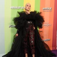 Penyanyi Christina Aguilera berpose saat tiba menghadiri 10th amfAR Gala di Los Angeles, California (11/10/2019). Aguilera tampil anggun dengan gaun hitam serta celana merah berkilau. (AFP Photo/Gregg DeGuire)