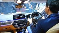 Hamish Daud merasakan ruang kemudi BMW Seri 5. (Septian/Liputan6.com)
