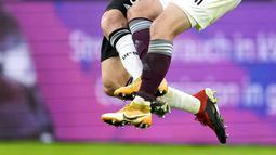 Bek timnas Jerman, Robin Gosens dan gelandang Latvia, Davis Ikaunieks bersaing dalam laga uji coba jelang EURO 2020 di Merkur Spiel Arena, Selasa (8/6/2021) dini hari WIB. Timnas Jerman memenangkan pertandingan dengan skor 7-1 atas timnas Latvia. (AP Photo/Martin Meissner)