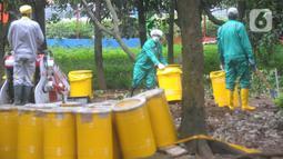 Petugas BATAN dan BAPETEN memasukkan tanah ke dalam drum saat proses dekontaminasi zat radioaktif di Perumahan Batan Indah, Tangerang Selatan, Minggu (16/2/2020). Petugas mengambil sisa-sisa tanah yang masih mengandung zat radioaktif untuk dibawa ke Batan guna diolah. (merdeka.com/Arie Basuki)