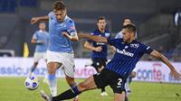 Striker Lazio, Ciro Immobile, berusaha melewati pemain Atalanta, Rafael Toloi, pada laga Liga Italia di Stadion Olimpico, Roma, Rabu (30/9/2020). Atalanta menang dengan skor 4-1. (Alfredo Falcone/LaPresse via AP)