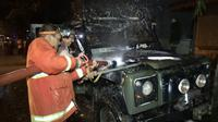 Petugas PMK berupaya memadamkan api yang membakar Land Rover 1961 milik mantan Wabup Tulungagung (Liputan6.com/Zainul Arifin)