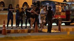 Tentara mengawal pengunjung yang keluar dari mal Terminal 21 Korat saat terjadi penembakan di Nakhon Ratchasima, Thailand, Minggu (9/2/2020). Akibat penembakan tersebut sebanyak 20 orang tewas. (AP Photo/Sakchai Lalitkanjanakul)