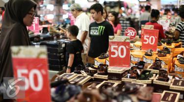 Pengunjung berburu sepatu baru di pusat perbelanjaan di Jakarta, Senin (3/7). H-2 Lebaran, sebagian pusat perbelanjaan masih dipadati pembeli yang mencari keperluan seperti pakaian dan celana dengan harga miring. (Liputan6.com/Faizal Fanani)