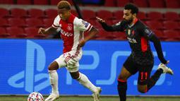 Penyerang Liverpool, Mohamed Salah, mengejar pemain Ajax Amsterdam, David Neres, pada laga Liga Champions di Stadion Johan Cruyff, Kamis (22/10/2020). Liverpool menang dengan skor 1-0. (AP/Peter Dejong)