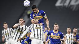 Pemain Juventus Alex Sandro (tengah) melompat untuk merebut bola dengan pemain Parma Graziano Pelle (atas) pada pertandingan Serie A di Stadion Allianz Turin, Italia, Rabu (21/4/2021). Juventus menang 3-1. (Piero Cruciatti/LaPresse via AP)