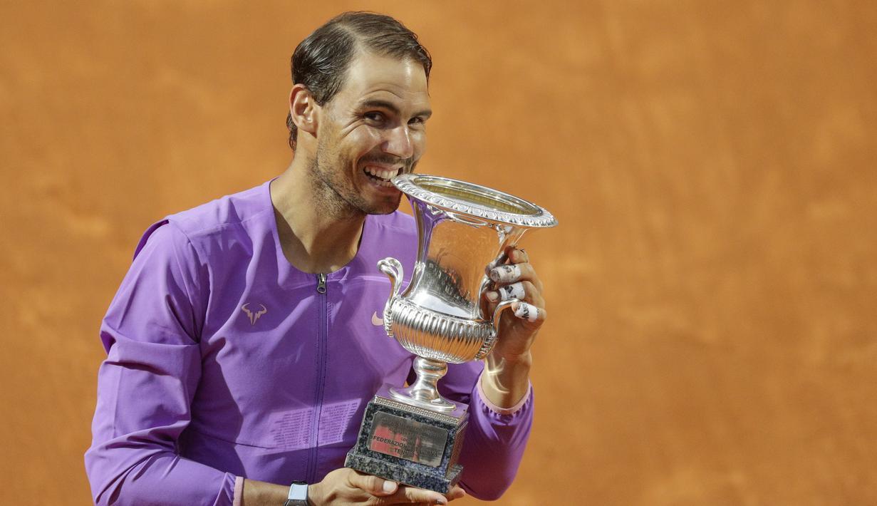 Petenis Spanyol, Rafael Nadal menggigit trofi juara turnamen tenis Italia Terbuka 2021 setelah mengalahkan petenis Serbia, Novak Djokovic di Foro Italico, Roma, Minggu (16/5/2021). Rafael Nadal menang dalam pertarungan tiga set 7-5, 1-6, dan 6-3 selama dua jam 49 menit. (AP Photo/Gregorio Borgia)