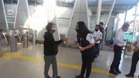 Pembagian Hand Sanitizer Spray BigRoot Care Sang Pisang aroma pisang secara gratis kepada penumpang kereta KRL tujuan Bogor ke Jakarta, Stasiun Bogor, Rabu (4/8/2021).
