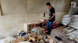 Seorang pria memeriksa barang bukti minuman keras Cap Tikus di Polres Gorontalo, Kamis, (24/1). Sebanyak 1,5 ton Cap Tikus tersebut diselundupkan dari Sulawesi Utara ke Gorontalo menggunakan mobil Avanza. (Liputan6.com/Arfandi Ibrahim)