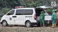 Petugas mengenakan APD saat mengeluarkan jenazah korban Covid-19 dari ambulans di TPU Tegal Alur, Jakarta, Kamis (25/6/2020). Menurut petugas makam TPU Tegal Alur, selama masa PSBB Transisi jumlah pemakaman jenazah dengan protap Covid-19 meningkat dibanding bulan lalu. (merdeka.com/Iqbal S Nugroho)