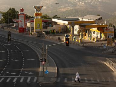 Seorang pria mengenakan syal sembahyang berjalan melintasi jalan utama saat peringatan Yom Kippur, atau Hari Pendamaian, yang berlangsung ketika Israel memberlakukan penguncian nasional (lockdown) selama tiga minggu, di Yerusalem pada Senin (28/9/2020). (AP Photo/Maya Alleruzzo)