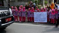 Murid TK Islam RA Baitul Ilmi melambaikan tangan saat rombongan Kahiyang-Bobby melintas di Jalan STM, Kota Medan, Sumatera Utara, Selasa (21/11/2017). (Liputan6.com/Johan Tallo)