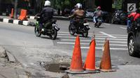 Pengendara menghindari jalan berlubang di kawasan Tanjung Barat, Jakarta, Rabu (30/1). Kondisi jalan rusak tersebut telah beberapa kali menyebabkan kecelakaan sehingga butuh penanganan. (Liputan6.com/Immanuel Antonius)
