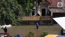 Warga melintasi banjir akibat jebolnya tanggul karena tertimpa tanah longsor, di Perumahan Nerada Estate Ciputat, Tangerang Selatan, Sabtu (12/6/2021). Longsor yang menimpa sejumlah rumah membuat tanggul pembatas kali jebol dan air meluap sehingga menyebabkan banjir. (Liputan6.com/Angga Yuniar)