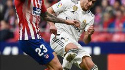 Gelandang Real Madrid,  Lucas Vazquez berebut bola dengan striker Atletico Madrid, Vitolo selama pertandingan lanjutan La Liga Spanyol di stadion Wanda Metropolitano (9/2). Real Madrid menang 3-1 atas Atletico. (AFP Photo/Pierre-Philippe Marcou)