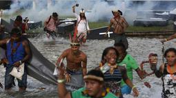 Sejumlah orang dari suku asli Brasil menggelar aksi di luar gedung Kongres Nasional di Brasilia, Brasil (25/4). Pemimpin adat suku asli tersebut meminta Presiden Brasil untuk mengembalikan perlindungan di berbagai wilayah Amazon. (AP Photo/Eraldo Peres)
