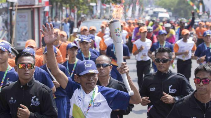 Legenda balap sepeda Indonesia, Sutiyono, membawa obor pada pawai Asian Games di Bandar Lampung, Rabu (8/8/2018). (Bola.com/Reza Bachtiar)#source%3Dgooglier%2Ecom#https%3A%2F%2Fgooglier%2Ecom%2Fpage%2F%2F10000