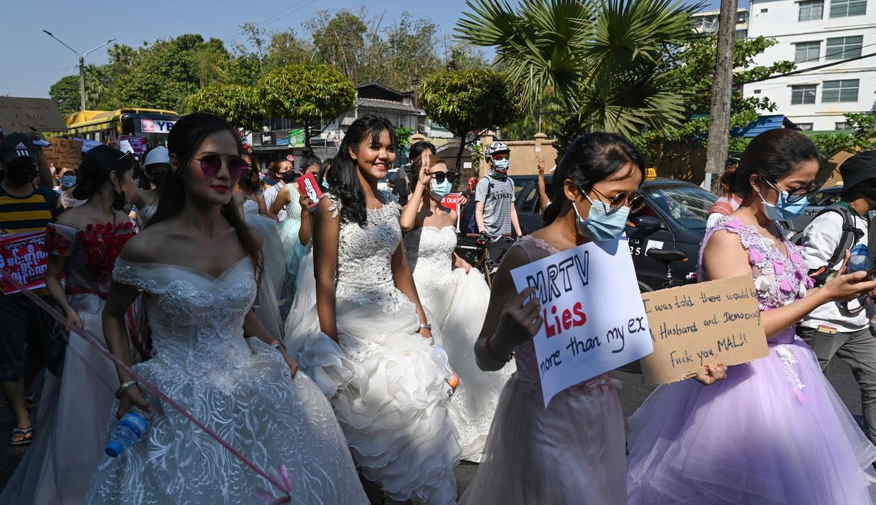 Wanita Myanmar memakai gaun pengantin memegang plakat selama demonstrasi menentang kudeta militer 1 Februari di Yangon (10/2/2021). (AFP/ Ye Aung Thu)